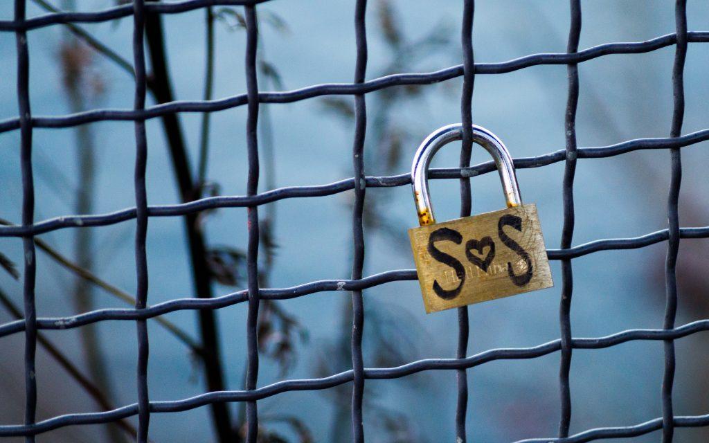 cadenas avec l'inscription SOS  accroché à une grille métallique