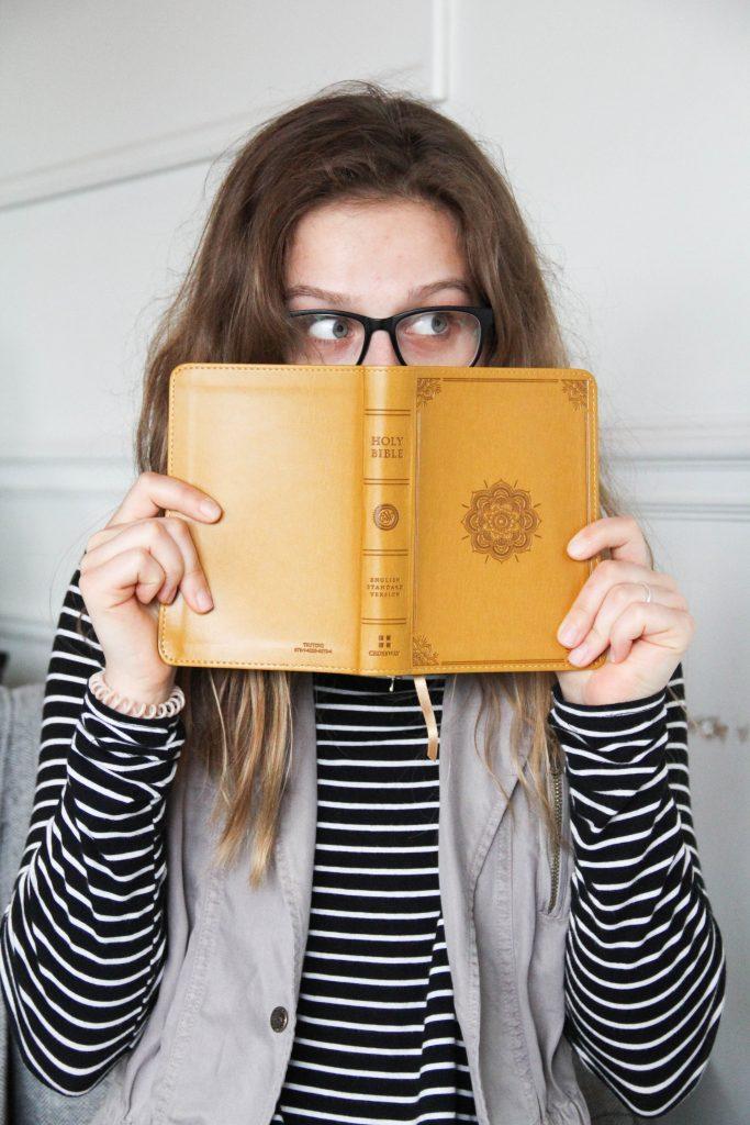 Une jeune fille tient une Bible ouverte devant son visage. On ne voit que le haut de son visage et ses yeux, qui trahissent un grand étonnement.