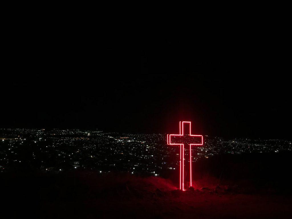 une grande croix est allumée dans la nuit avec les lumières d'une ville en arrière-fond