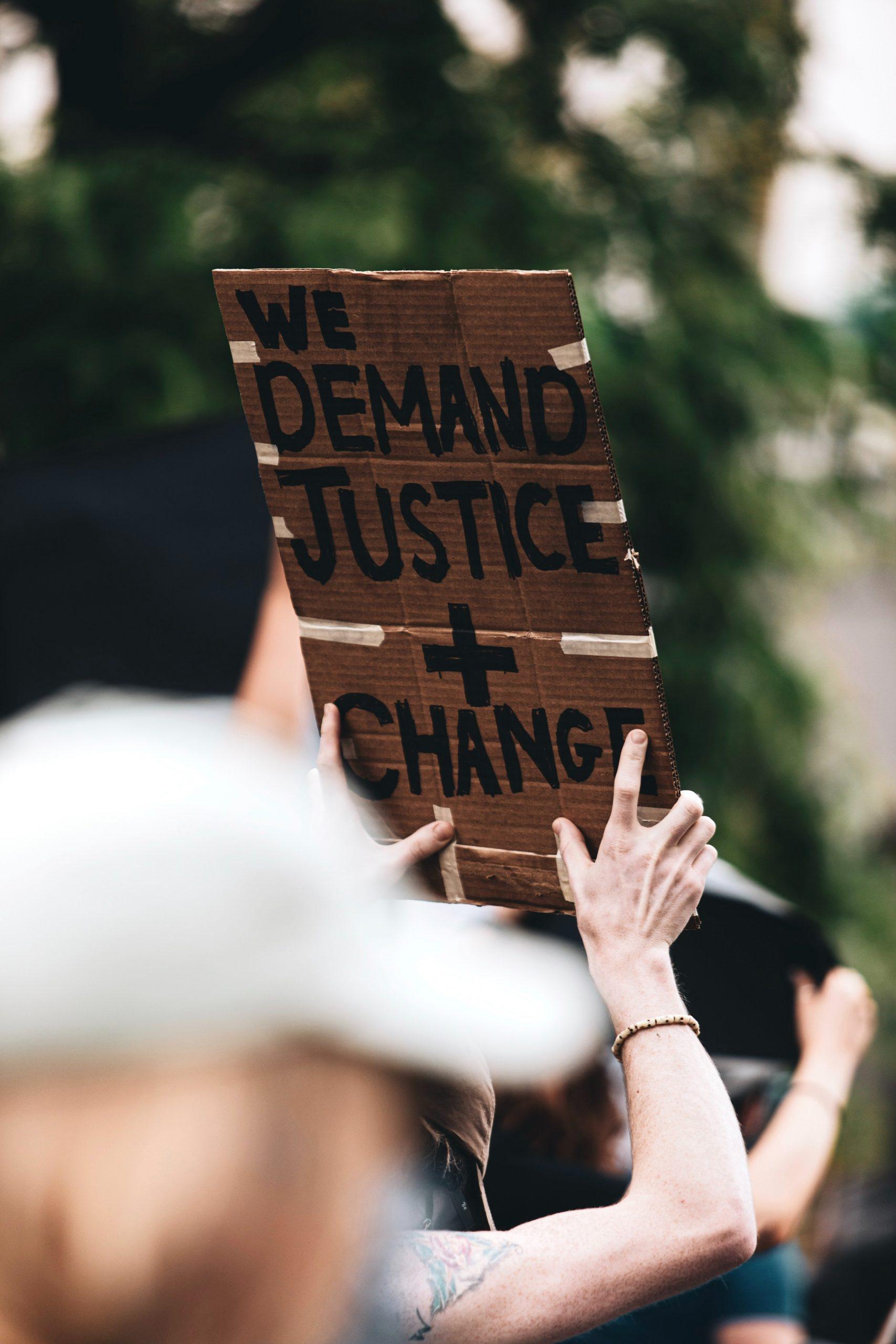 """manifestant brandissant une pancarte avec l'inscription (anglais) """"nous demandons la justice + le changement"""""""
