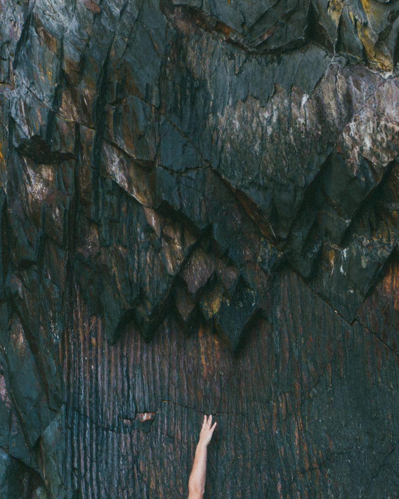 une paroi rocheuse, pierres foncées et lisses, avec un bras tendu au bas de l'image, main légèrement entrouverte, symbolisant le caractère désespérant de la foi  à l'épreuve de la souffrance
