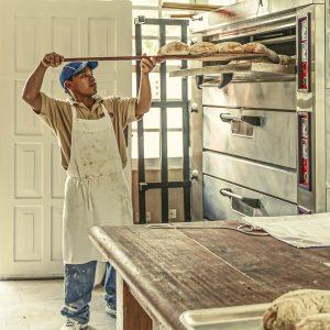 un boulanger en train d'enfourner du pain dans son four