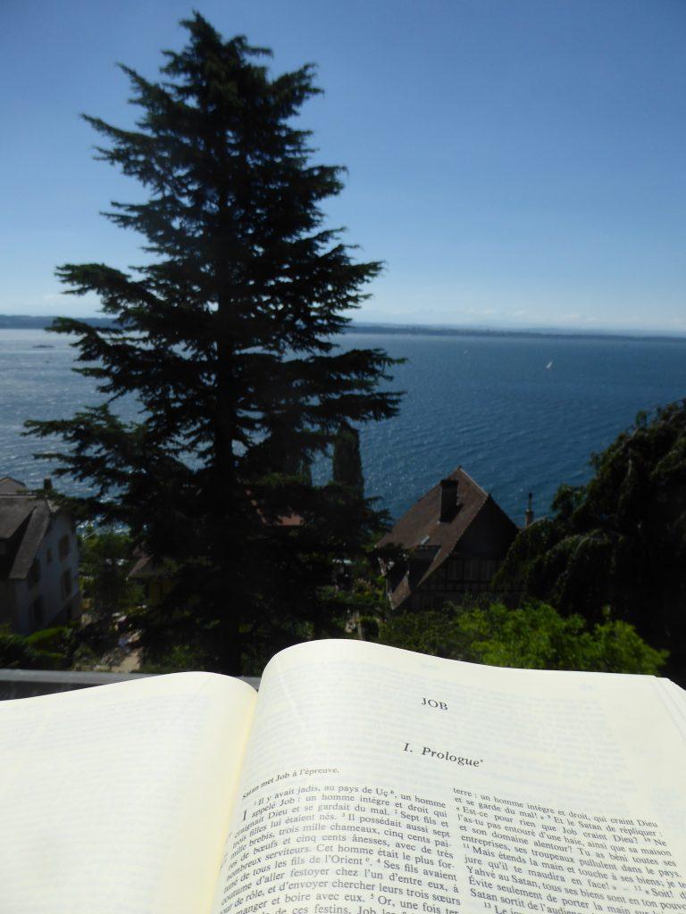 la Bible ouverte à la première page du livre de Job avec une vue sur le lac