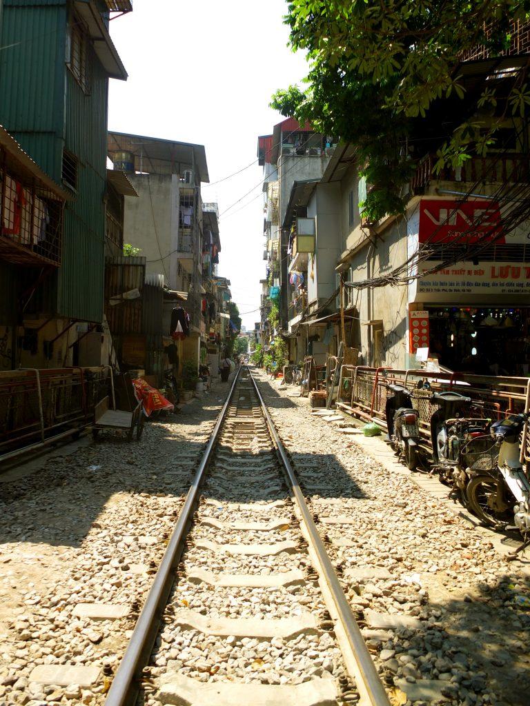 une voie de chemin de fer, droite dans une ville probablement en Inde
