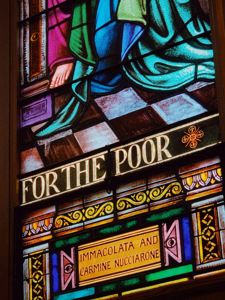 """Une section de vitrail, avec l'inscription en anglais """"For the poor"""" (pour le pauvre)."""
