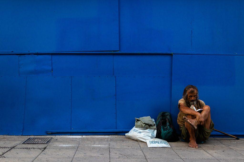 un homme seul, visiblement pauvre comme Job, sans abri, assis sur le trottoir, au bord d'un bâtiment