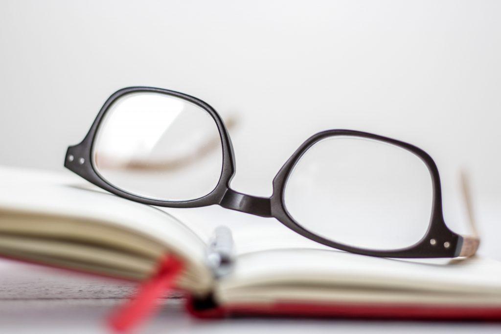 Une paire de lunettes posée sur un livre ouvert