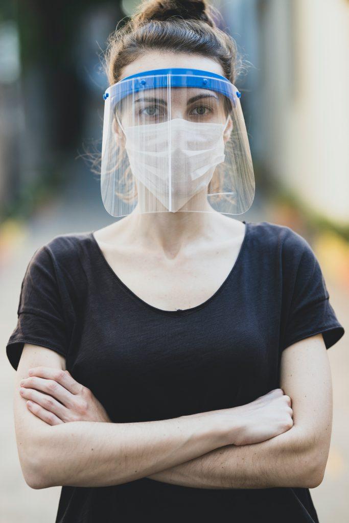 Faire tomber les masques, vraiment ? Une jeune femme portant masque et visière ne plexiglas. elle nous regarde droit dans les yeux et croise les bras
