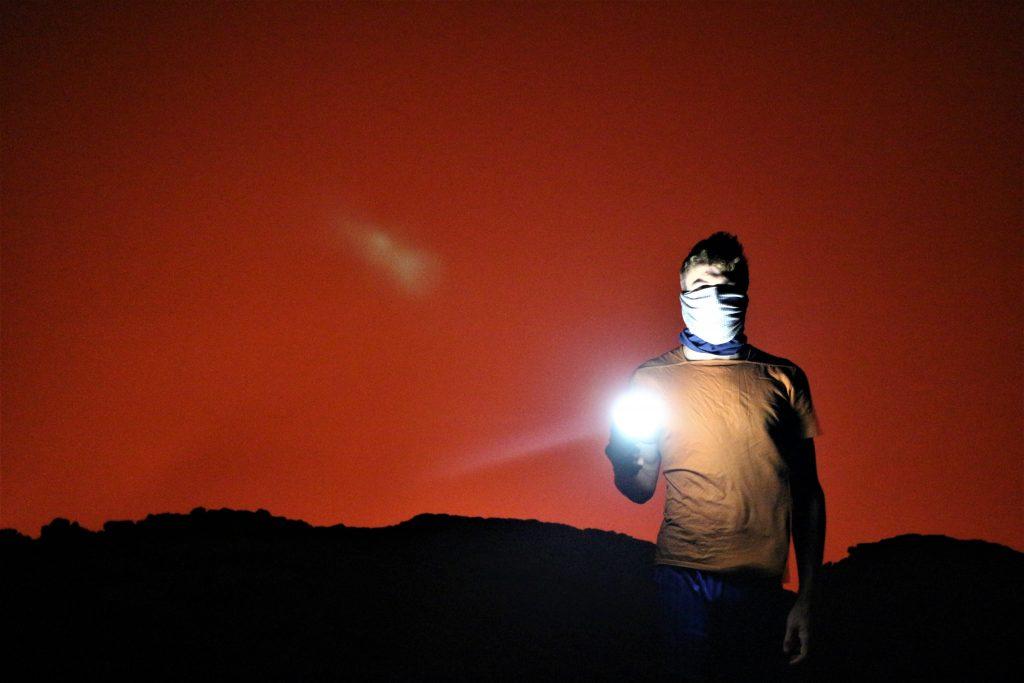 Faire tomber les masques, vraiment ? Au crépuscule, un homme masqué tient une lampe de poche et nous éclaire à la tombée de la nuit